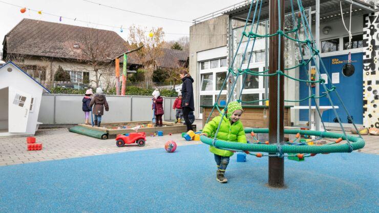 Des enfants jouent à l'exterieur de la crèche Chemin des Oeuches. On voit un bac à sable, une petite maison de jardin et une pyramide tournante.
