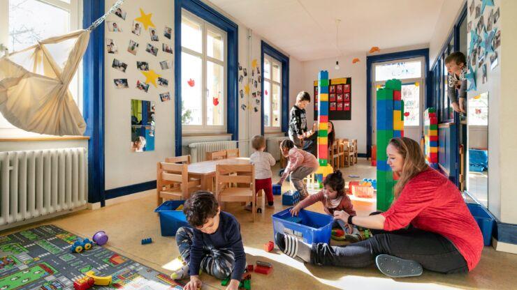 On voit une salle lumineuse avec beaucoup de jouets et de nombreux enfants qui s'amusent.