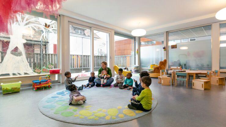 Les enfants et une animatrice sont assis dans un grand cercle et chantent.