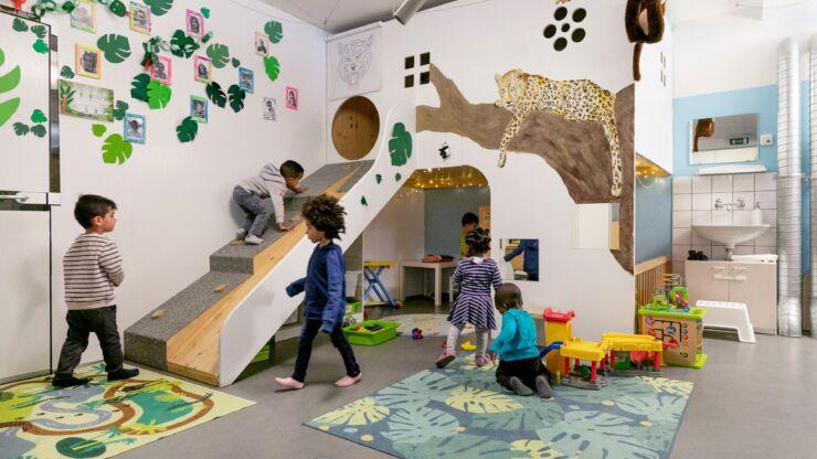Des enfants s'amusent dans une maisonnette de jeux et sur un toboggan.