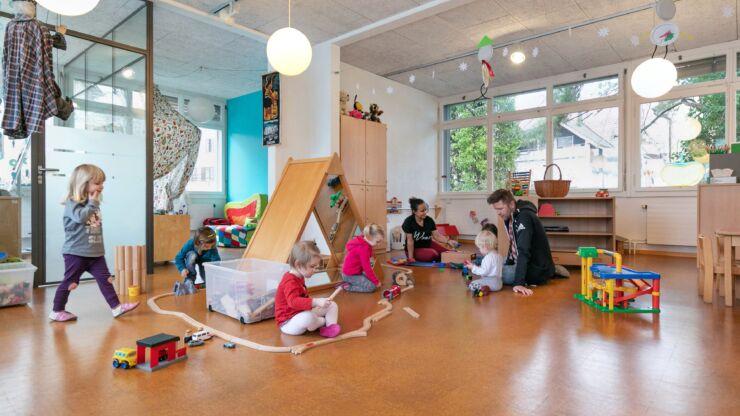 Les enfants jouent avec une éducatrice et un éducateur dans une pièce lumineuse de la crèche Soleil.