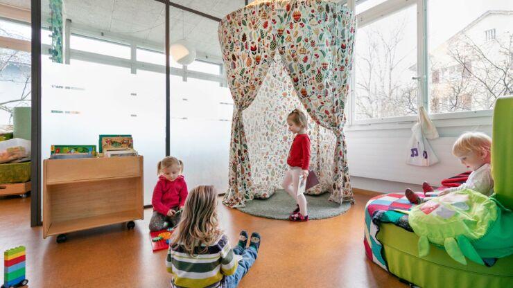 Die gemütlich eingerichtete Bücher-Ecke der Kita ist zu sehen. Kinder schauen Kinderbücher an.