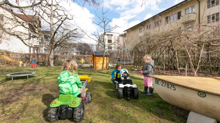 Kinder spielen im grossen Garten der Kita. Man sieht unter anderem ein Trampolin, eine Rutschbahn, eine Schaukel, einen drehbaren Kletterturm und Spielzeug-Traktore.
