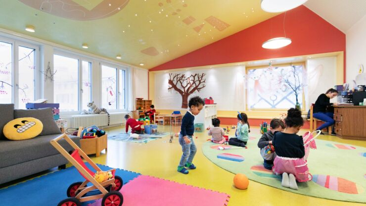 On voit une grande salle lumineuse et accueillante avec de nombreux jouets et des enfants qui s'amusent.
