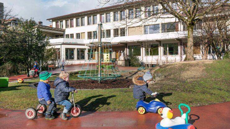 Des enfants jouent sur des petits véhicules dans le jardin de la crèche.