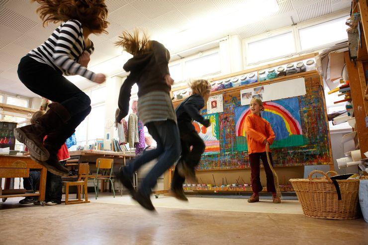 Foto des Freizeitateliers. Im Vordergrund sieht mau drei in die Luft springende Kinder, im Hintergrund steh ein Mädchen vor einer Malwand.