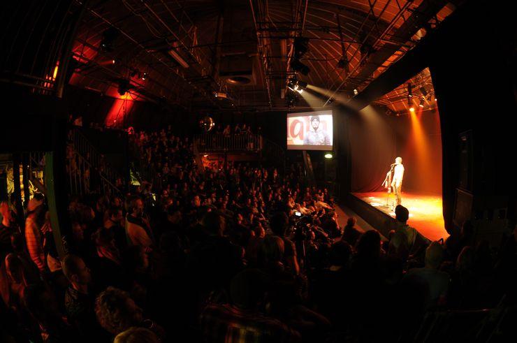 Une grande salle sombre et pleine de monde. Sur la droite se trouve une scène avec un homme debout devant un microphone. Il y a des points lumineux jaunes et rouges, qui sont principalement destinés à l'homme sur scène. A côté, vous pouvez également voir une projection à l'écran de la scène.