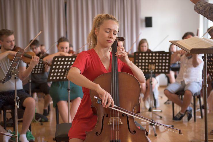 Dans une grande salle il y a beaucoup de jeunes qui jouent des instruments à cordes. Devant eux se trouvent les pupitres à musique. Au centre de l'attention se trouve une jeune femme blonde en robe rouge qui a les yeux fermés pendant qu'elle joue du violoncelle.