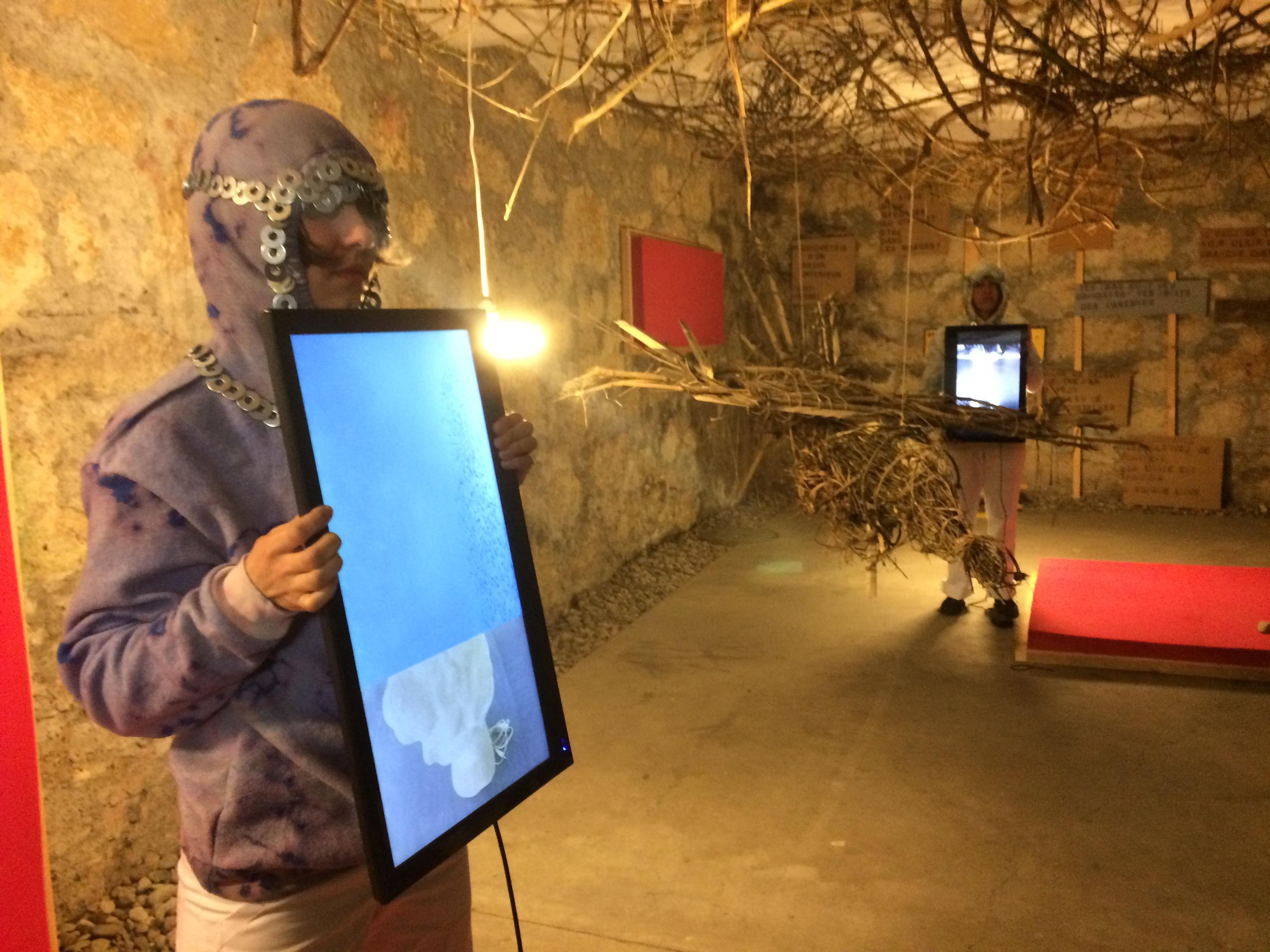 In einem Zimmer mit Steinwänden kommen Holz Äste von der Decke. Und zwei Menschen in ritterähnlichem Kostüm halten je ein Display in den Händen. Auch sind mehrere rote Rechtecke im Raum verteilt.
