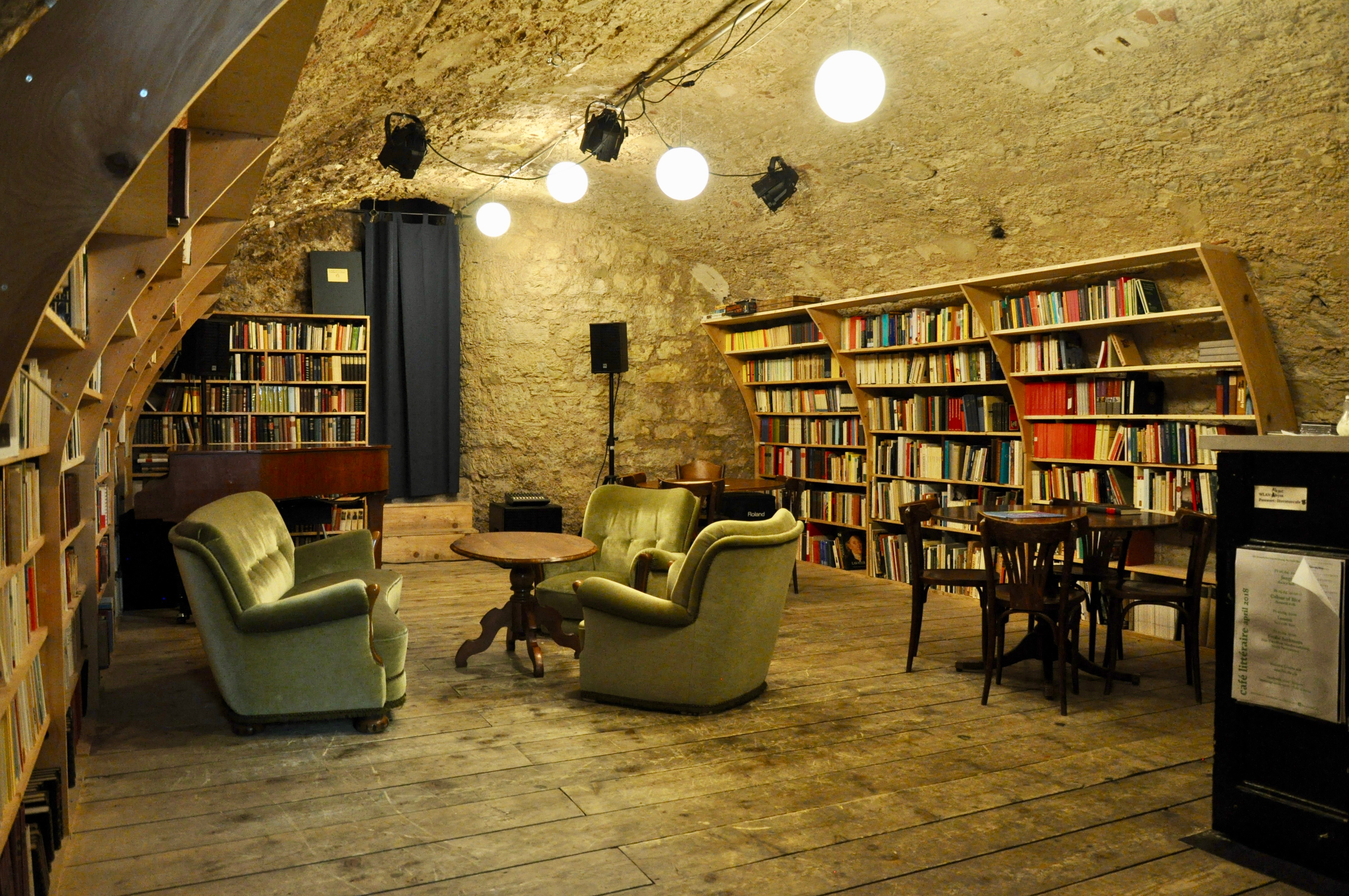 Dans une pièce avec un plancher de bois et des murs de pierre, il y a beaucoup de livres sur les étagères et divers styles de sièges, ainsi qu'un système de musique.