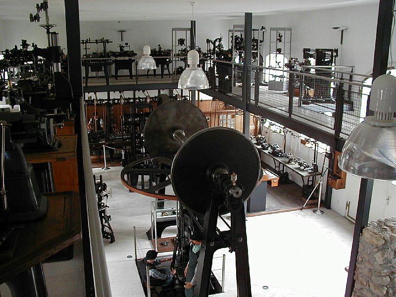 Ein grosser, hoher Raum, mit mehreren Etagen, worin sich viele metallene Maschinen befinden.