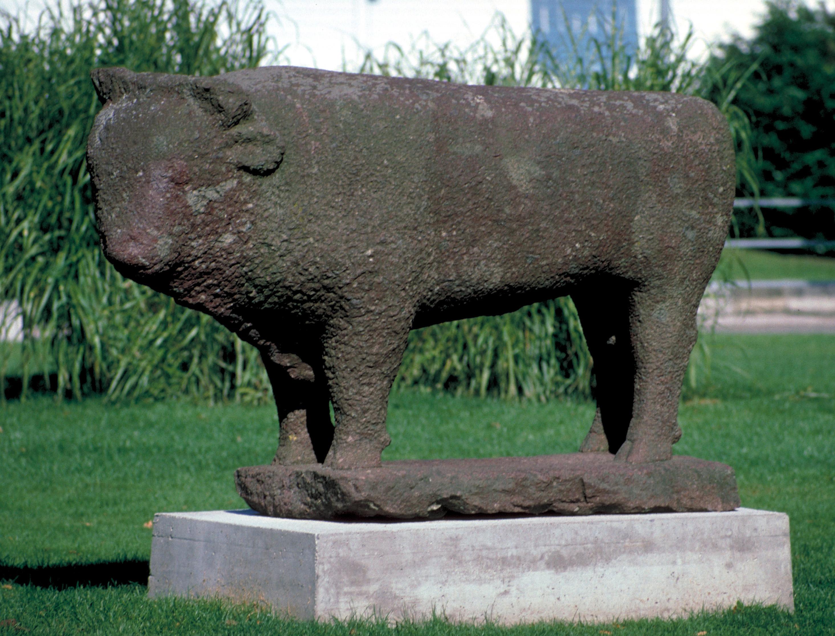 Une grande sculpture en pierre repose sur un piédestal dans une prairie. Il a la forme d'un taureau.