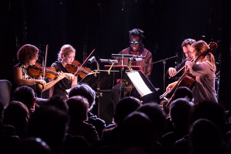 Im Fokus sind 5 Musizierende: 3 Frauen und 2 Männer im Halbkreis sitzend mit Streichinstrumenten in der Hand. Davor befinden sich viele Zuschauer.