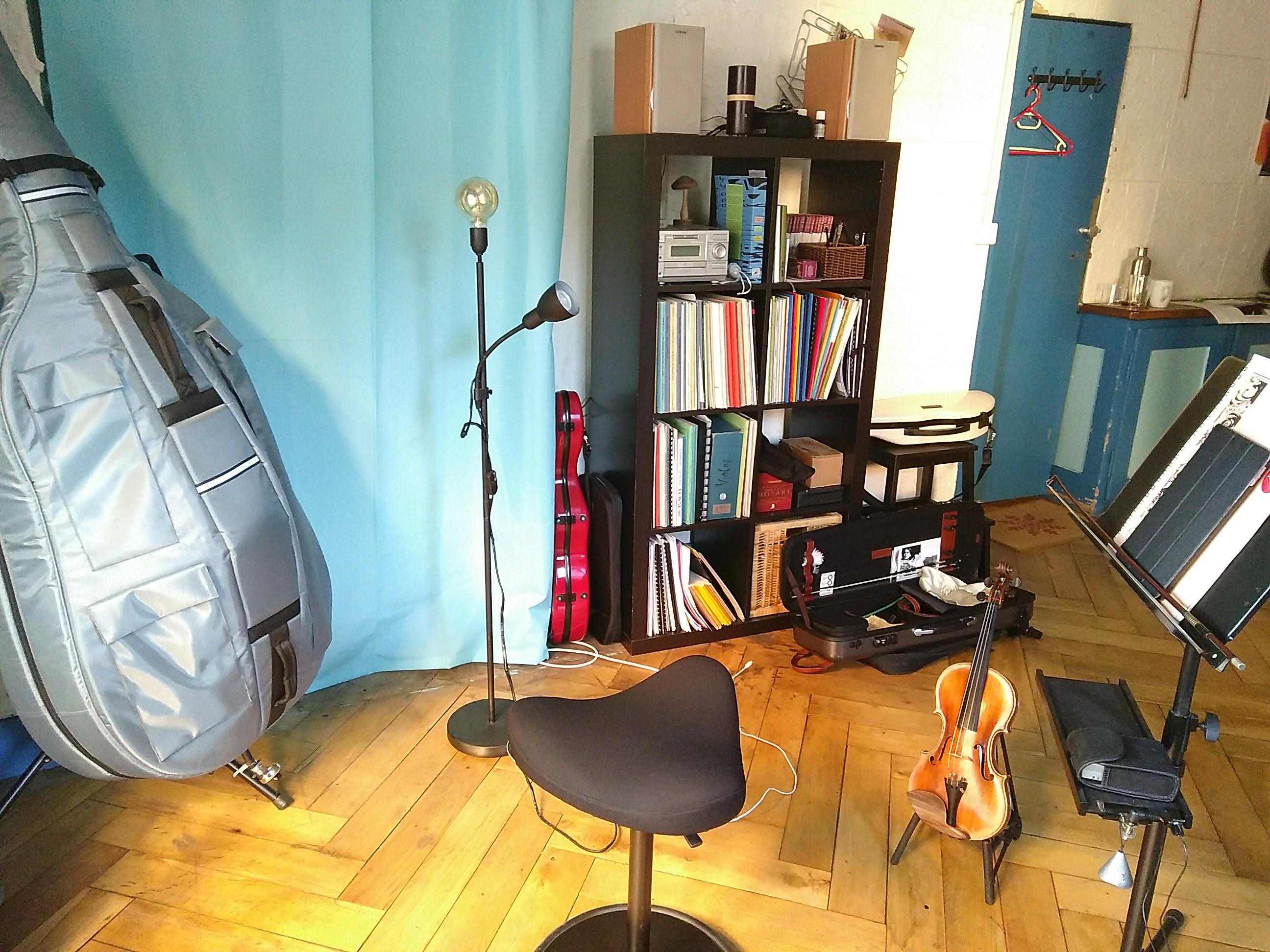 Ein kleines Zimmer mit Holzboden und blauem Vorhang. Darin befinden sich viele Notenblätter, eine Musikanlage und diverse Instrumente wie zum Beispiel eine Geige.