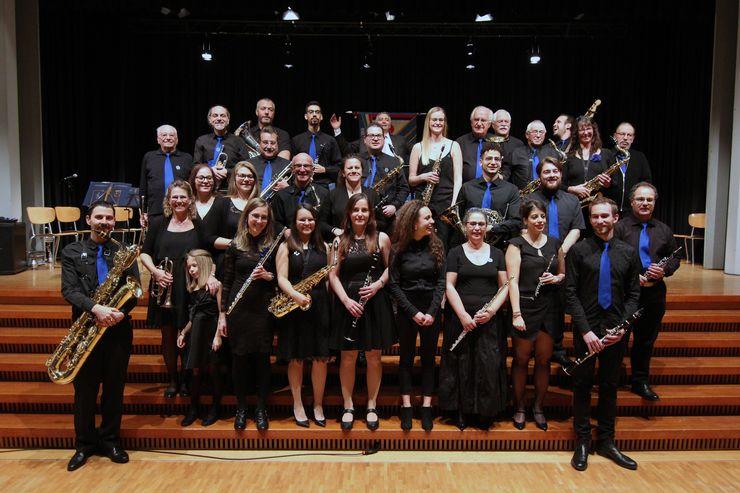 Eine Musikkappelle von etwa 30 Personen steht auf einer Treppe. Alle tragen schwarze Kleidung, die Männer zudem eine blaue Krawatte und alle halten ihre Musikinstrumente in der Hand.