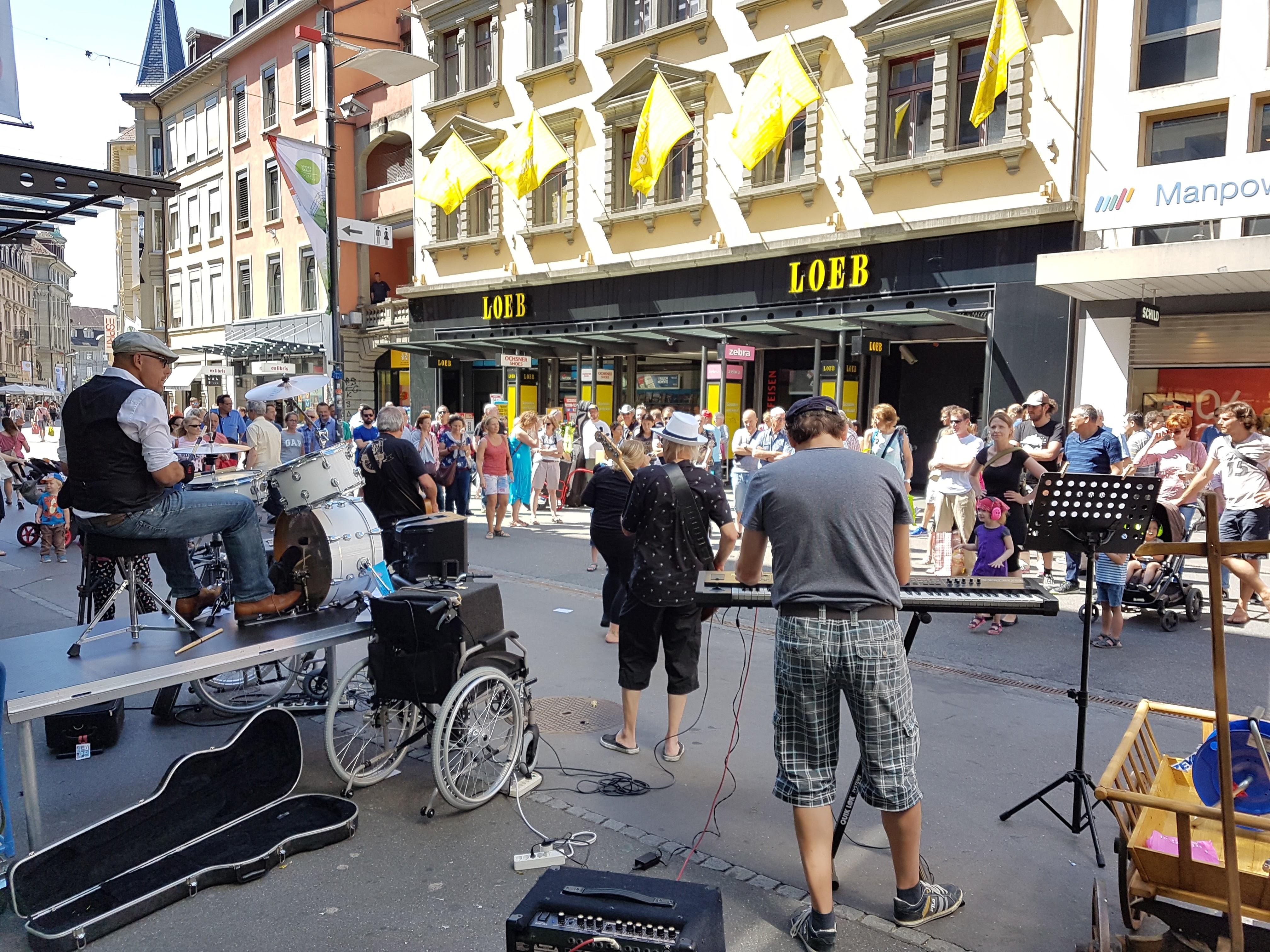 Auf einer Einkaufsstrasse haben sich viele Menschen um 4 Musiker herum versammelt. Diese bestehen aus einem Schlagzeug, einem E-Piano und 2 Gitarren.
