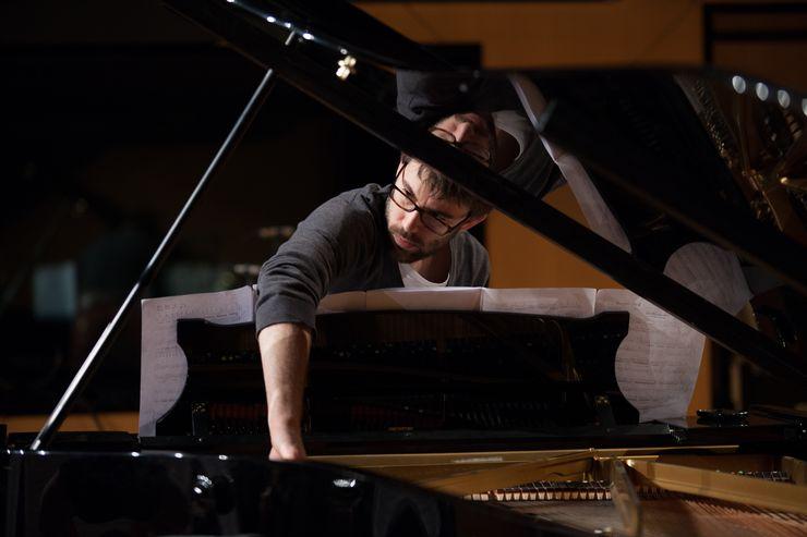 Ein Mann mit Brille über Notenblätter geneigt an einem Klavier.