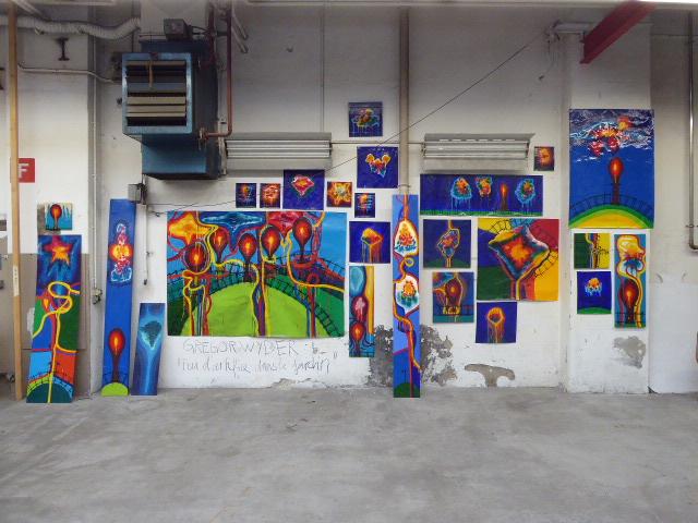 An einer weissen Wand sind viele kleinere und grössere Bilder aufgehängt. Sie sind sehr bunt.