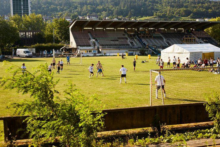 Auf einem grossen Rasen spielen Jugendliche miteinander Fussball. Im Hintergrund ist ausserdem ein Festzelt und eine Zuschauertribüne zu erkennen.