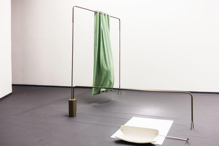 Il s'agit d'une sculpture faite de différentes barres de fer. Un rideau vert est suspendu à l'un d'eux. À côté, il y a quelque chose qui ressemble à un dossier de chaise sur un rectangle blanc. Le sol est noir, le mur blanc.