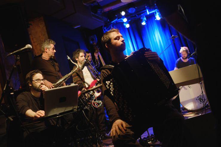 6 Männer spielen zusammen Musik: Einer davon ist am Akkordeon, einer an einem Laptop, dann gibt es ein Saxophon und zwei Männer im Hintergrund, wo man nicht erkennen kann, was sie machen.