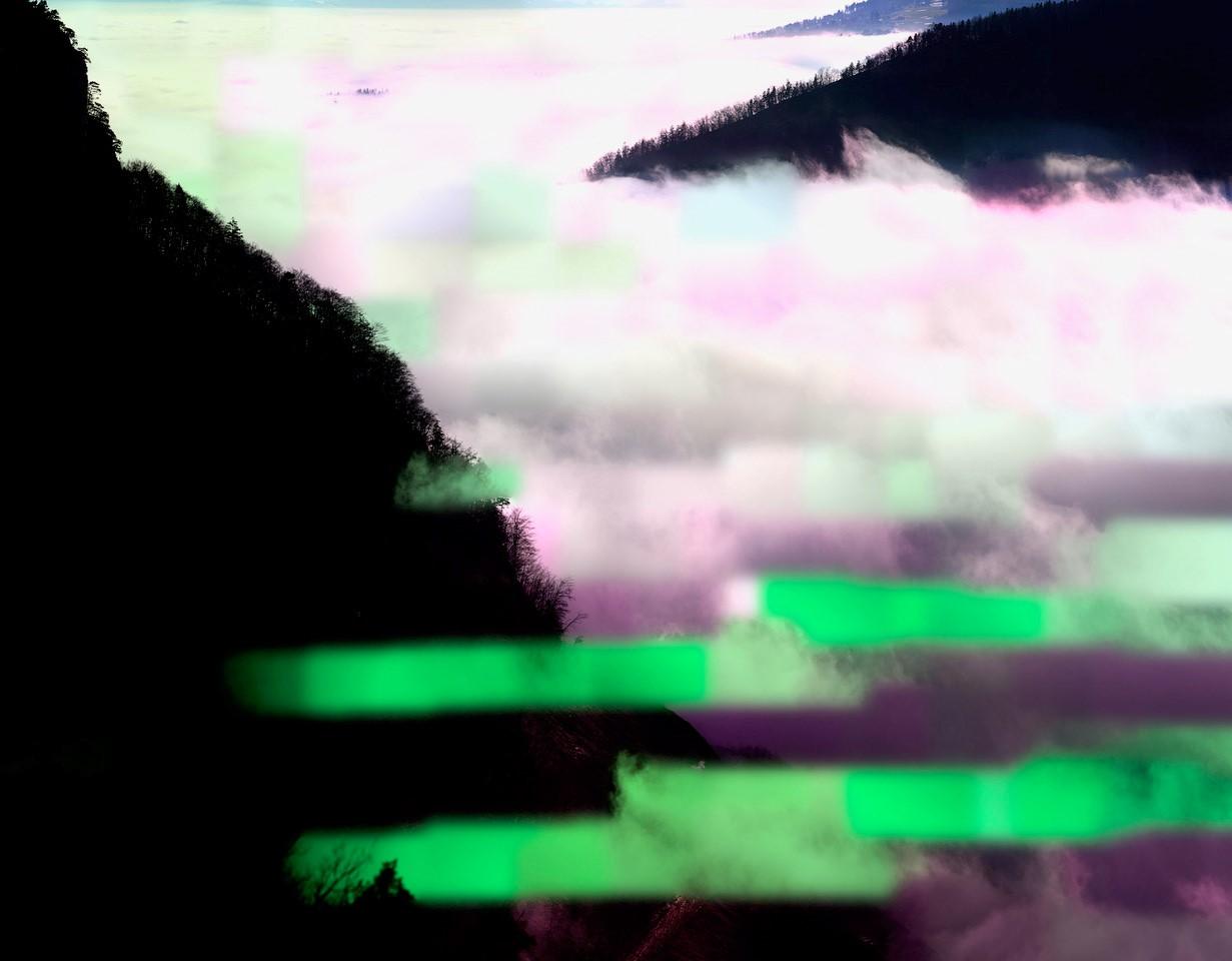 Eine Fotografie zeigt mit Nebel gefüllte Täler, die von dunklen Waldflächen umgeben sind. Speziell an dem Bild sind die unechten, grünen und violetten Bildstreifen.