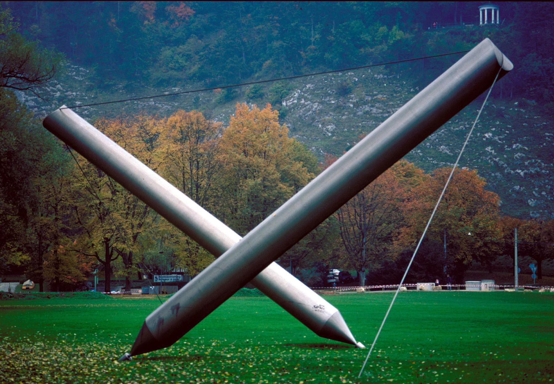 Auf einer Wiese ist eine grosse Skulptur aufgestellt. Dabei handelt es sich um zwei metallene Stifte, die aufgestellt sind, indem sie mit einem Draht gespannt sind. Die Stiftspitzen sind dabei die Berührungspunkte zum Boden.