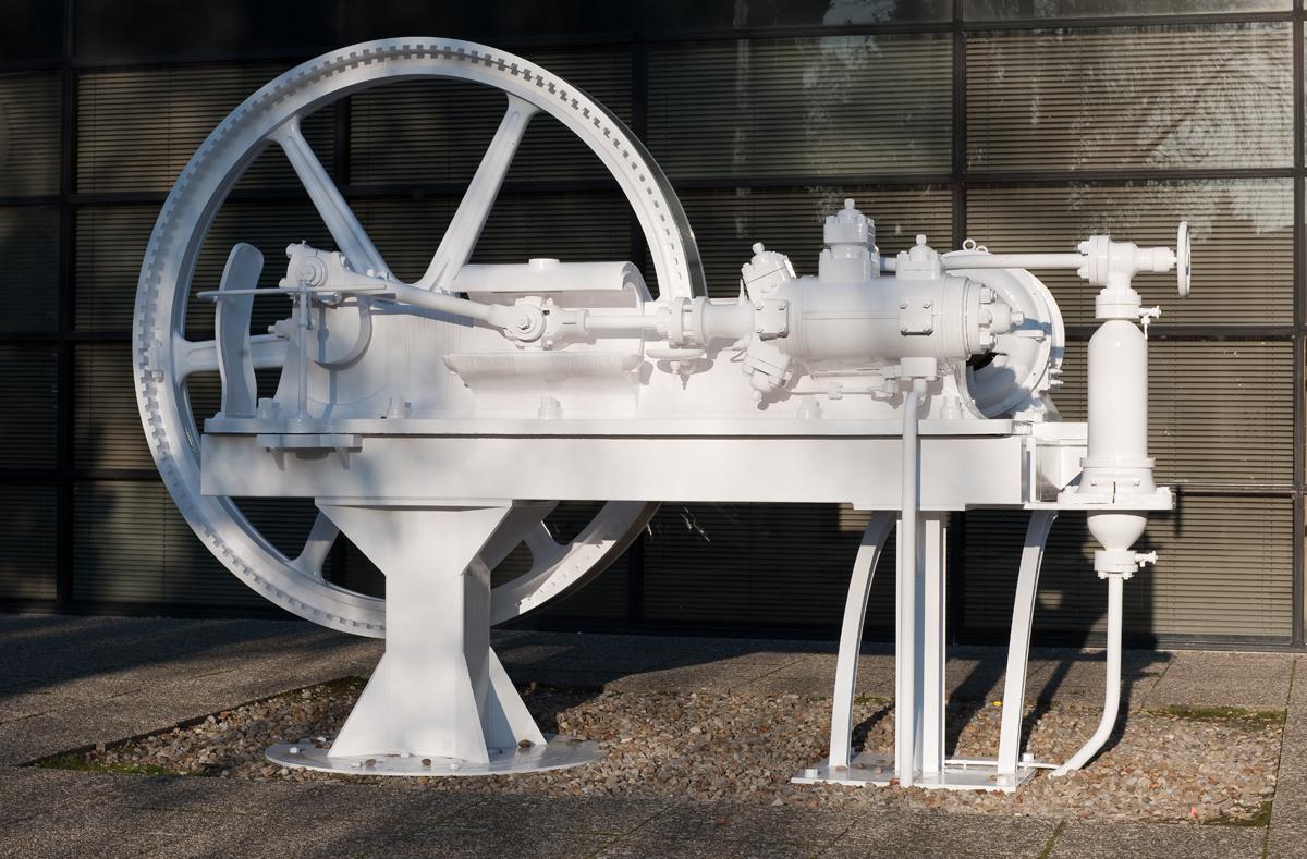 Une machine peinte en blanc sur un carré de pierre.