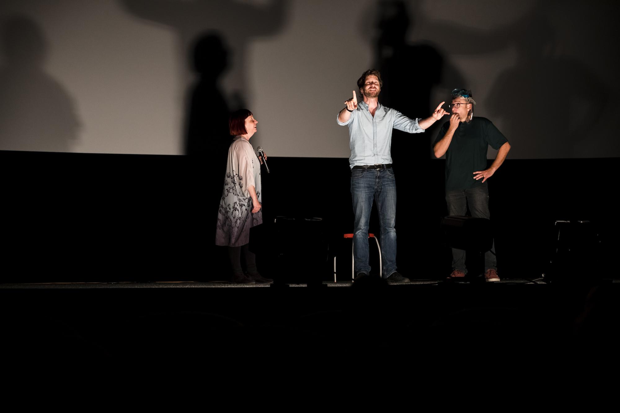 Auf einer Bühne sind zwei Männer und eine Frau mit Mikrofon beleuchtet. Der Mann in der Mitte hebt die Arbe und erzählt etwas, hinter ihm steht ein kleiner roter Hocker. Ansonsten ist es ziemlich dunkel.