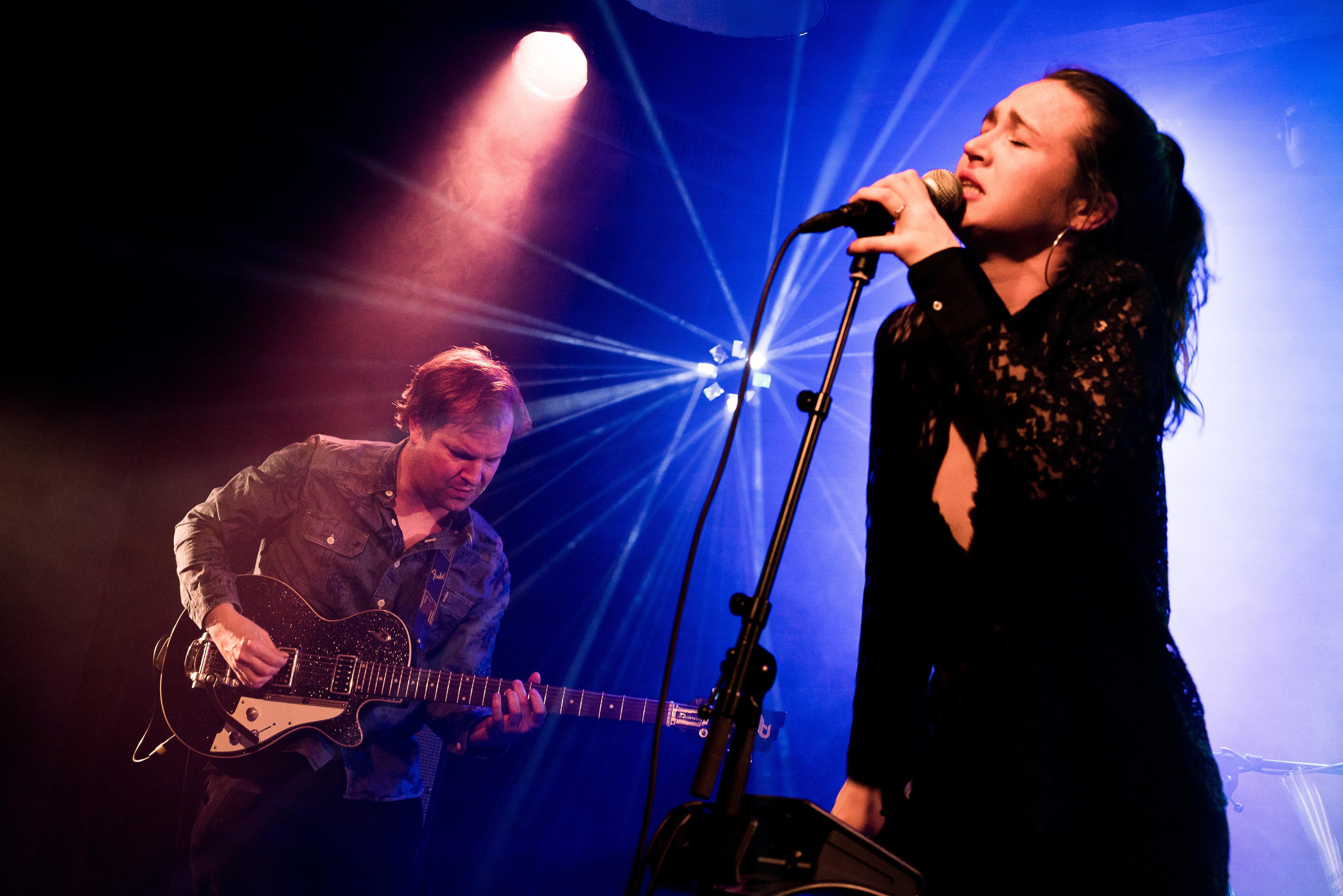 Auf einer Bühne, von einem Lichtspot beleuchtet machen zwei Leute Musik. Ein Mann an der Gitarre und eine Frau, die singt.