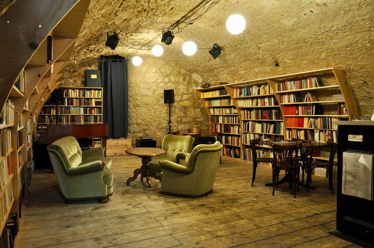 Cette chambre a des planchers de bois et des murs de pierre et à l'intérieur il y a beaucoup de livres dans les étagères. Il y a aussi diverses options de sièges et un système de musique.