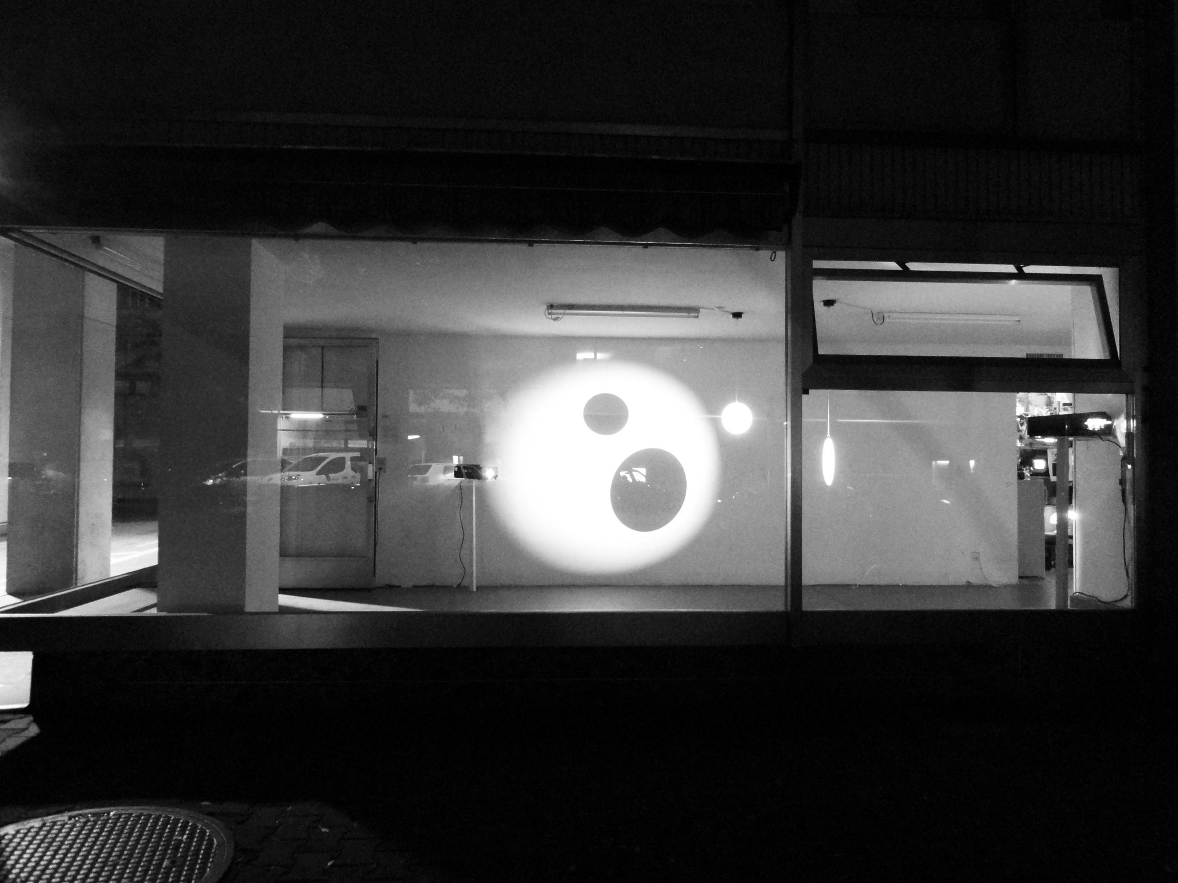 Dans une salle blanche avec deux grandes fenêtres, deux projecteurs sont installés qui projettent des formes rondes sur le mur.