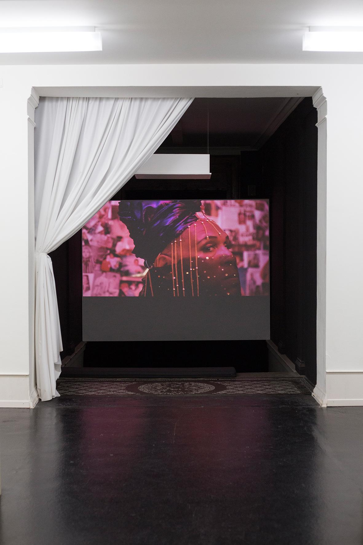 Durch eine grosse, offene Tür mit einem weissen Vorhang an der Seite erkennt man eine Bildprojektion auf der Wand. Darauf wird ein rötlich gefärbtes Bild ersichtlich, auf dem eine Frau mit Schleier und Kopfbedeckung ist. Ausserdem liegt vor der Wand ein orientalischer Teppich.