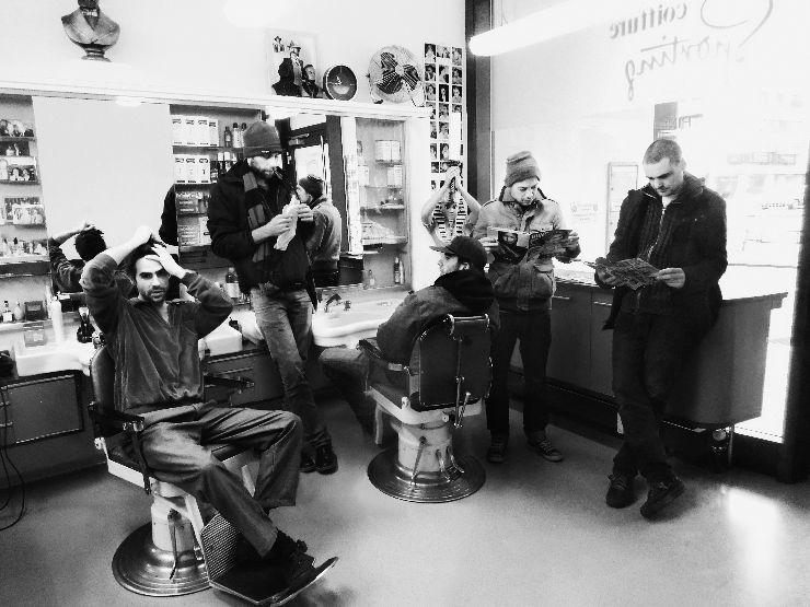 5 jeunes hommes, en partie assis, en partie debout dans un salon de coiffure. L'un mange un kebab, deux lisent dans un magazine, l'un passe dans ses cheveux et l'autre le regarde.