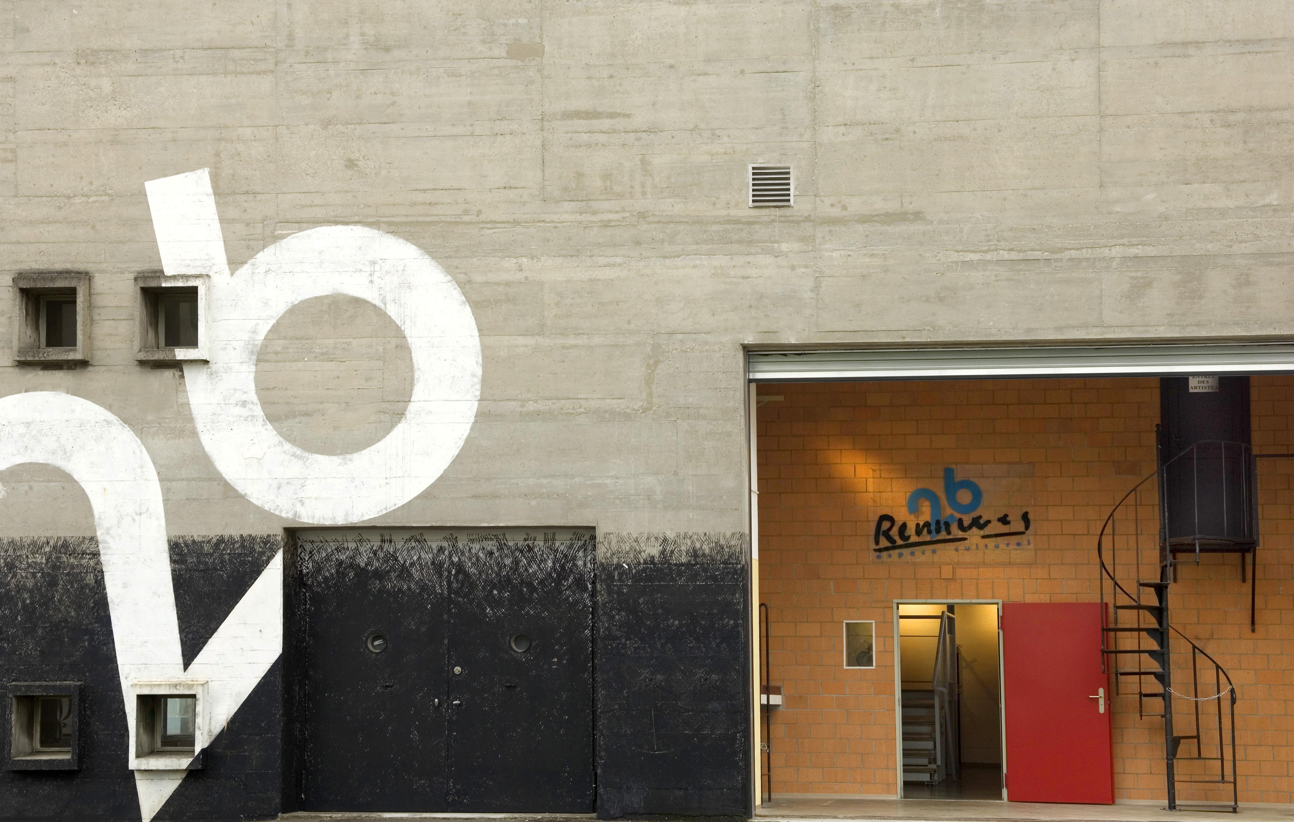 Eine Hausfassade einer offenen, roten Türe ist hier zu sehen. Daneben befindet sich eine schwarze Treppe und ein Schild mit der Aufschrift «Rennweg 26».
