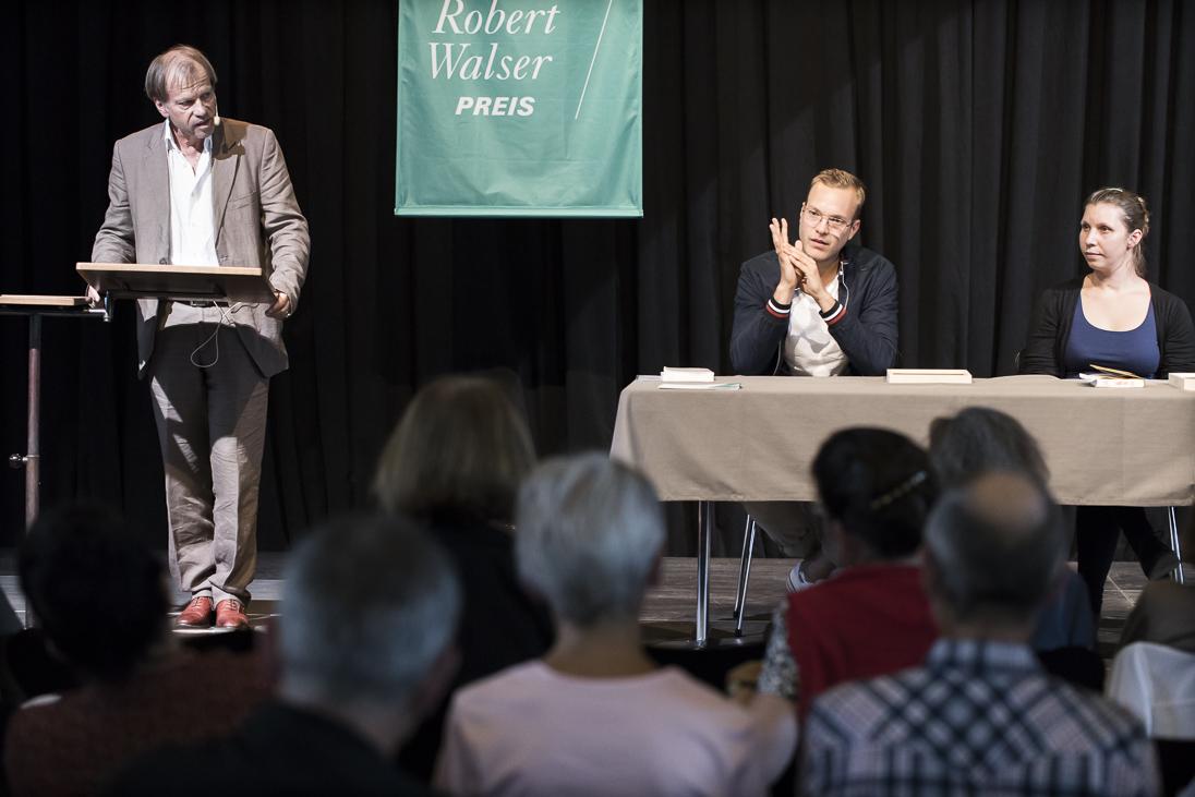 """Un homme en costume équipé d'un microphone se tient debout devant un lutrin et parle. A côté, un drapeau avec l'inscription """"Prix Robert Walser"""" et devant lui, un homme et une femme assis à une table, avec des livres étendus devant eux. On soupçonne aussi un public plus large devant lui."""