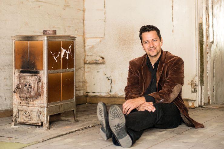 Un homme aux cheveux noirs, au costume noir et au blazer de velours brun est assis sur le sol, les bras croisés. A côté, un ouvre-bouteille marron. Le sol est en bois.