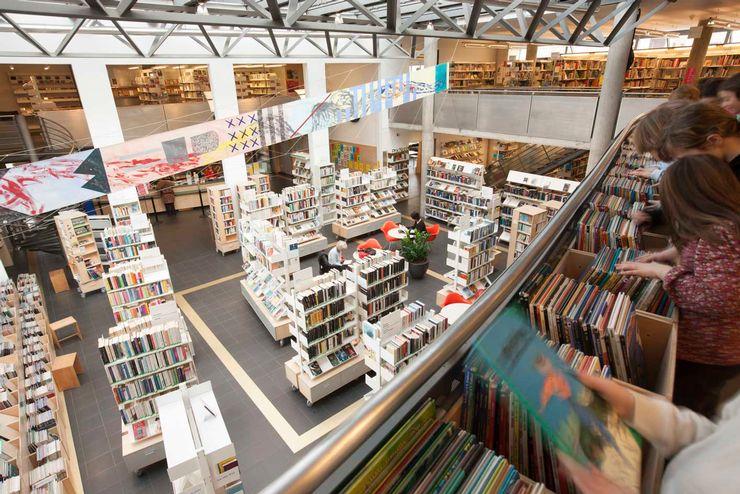 Une salle pleine de bibliothèques sur plusieurs étages. On voit quelques personnes regarder les livres et une banderole à travers la pièce.