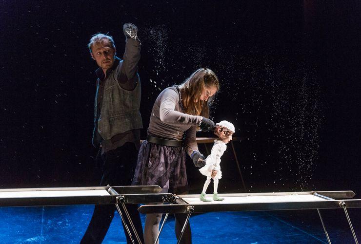 Une femme est penchée sur une poupée et la tient dans ses mains. Derrière, il y a un homme qui répand sa poudre sur ses épaules.