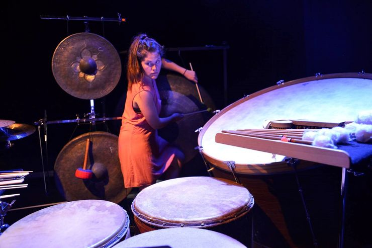 Eine Frau mit orangem Kleid und braunen Haaren spielt an der Percussion.
