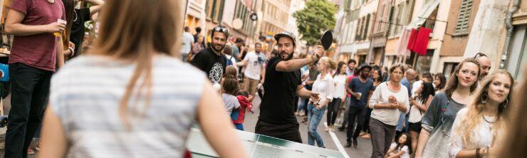 Un homme et une femme jouent au tennis de table ensemble au milieu de la foule.