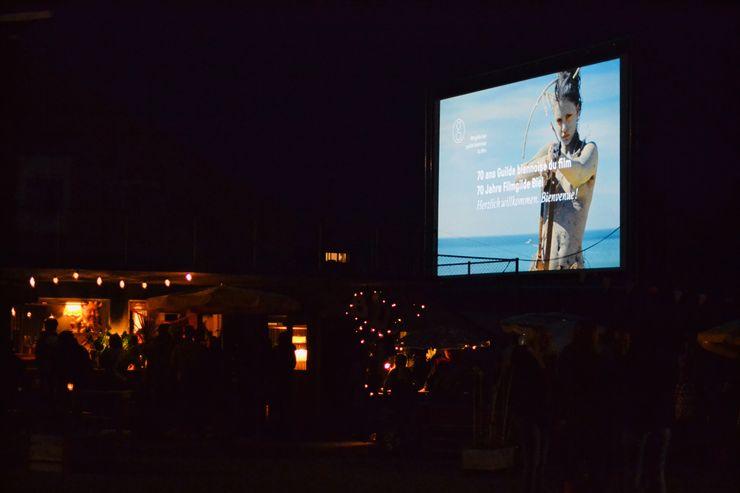 Es ist dunkel und man ist draussen. Auf der rechten Seit sieht man eine grosse Filmleinwand, auf der «70 Jahre Filmgilde Biel» geschrieben und eine angemalte Frau mit Pfeilbogen erkennbar ist.