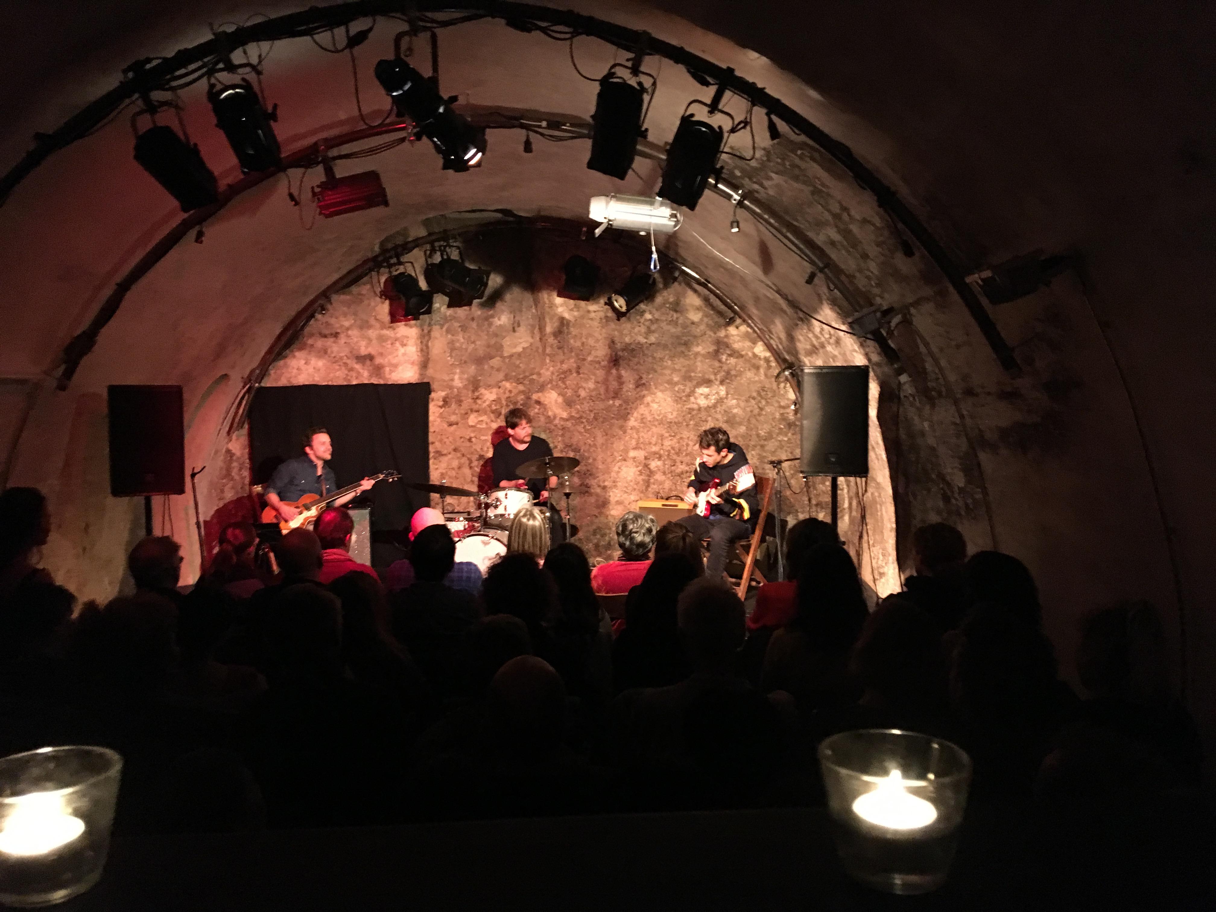 In einem gewölbten, steinernen Raum befinden sich drei Leute auf einer Bühne und machen Musik. Dahinter ist ein Publikum mit vielen Menschen zu sehen.