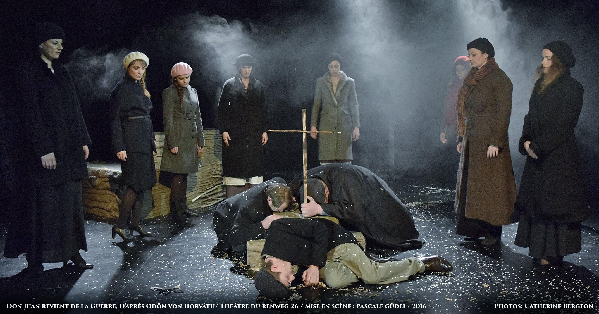 Drei Männer liegen zusammen gekauert auf dem Boden, ein Kreuz in den Händen. Darum hat sich ein Kreis Frauen gebildet die auf die Männer herabblicken. Alle tragen lange Mäntel und Kappen.
