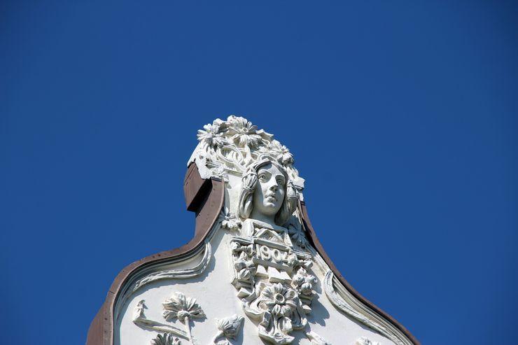 Auf diesem Foto ist ein weisses Denkmal ersichtlich, darauf abgebildet ist ein Frauenkopf und Blumen und das Jahr 1904.