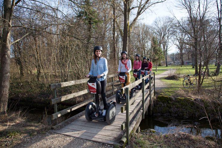 Eine Gruppe von 5 Menschen mit Helmen, die gerade auf Segways über eine Holzbrücke, über einen Bach fahren. In der Umgebung hat es viel Gras, Sträucher und Bäume.