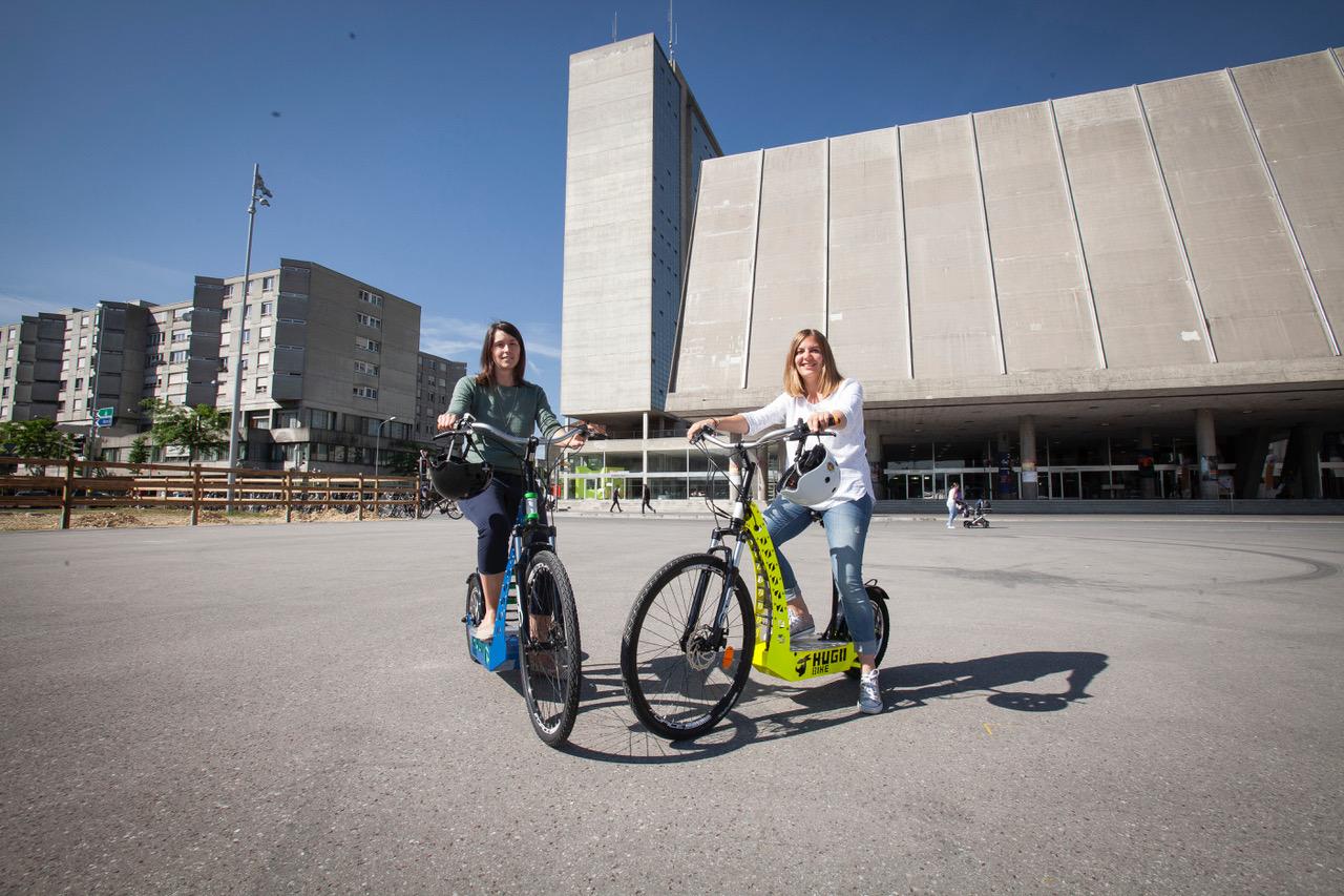 Zwei Frauen sitzen auf Hugo-Bikes, die auf einem grossen Betonplatz stehen. Im Hintergrund sieht man ein grosses modernes Gebäude und weitere Wohnblöcke.