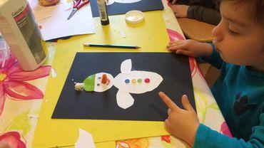 Deux enfants sont assis à une table et font un bricolage: ils collent un bonhomme de neige sur une feuille de papier noire.
