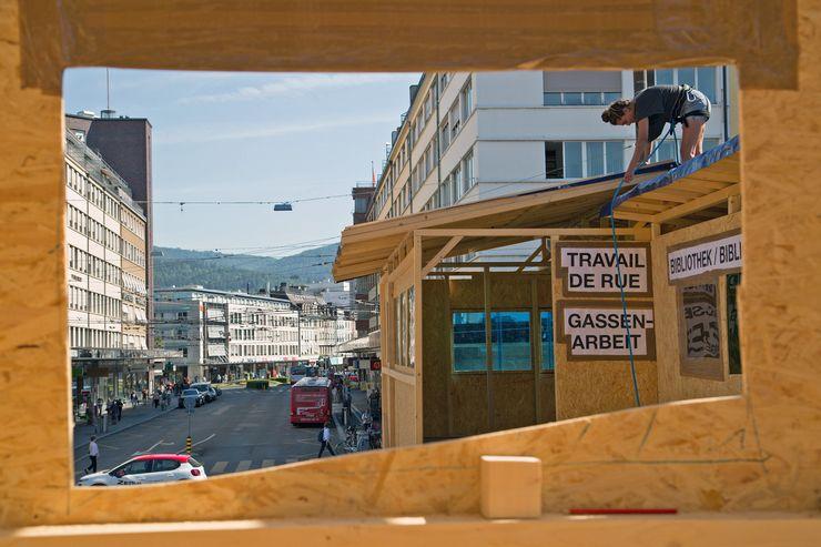 Durch das Loch einer Holzspanplatte sieht man auf eine Strasse und mehrere Gebäude. Zudem sind zwei Schilder ersichtlich, auf denen «Gassenarbeit» und «Bibliothek» zu lesen sind. Darüber auf dem Dach steht eine Frau, die etwas mit einer blauen Schnur macht.