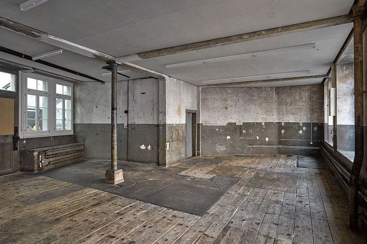 Man sieht einen grossen, leeren Raum, der rohe Betonwände mit Flecken und einem Holzboden, sowie offen gelegten Rohren hat. An der Decke befinden sich Neonröhren und links und rechts sind Fenster.